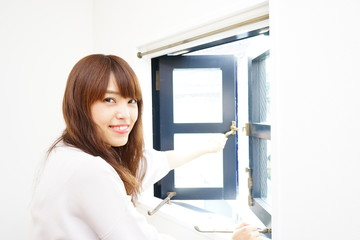 Young Japanese woman opening window