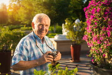 Man smiling and holding camera. Old male outdoors. Active leisure after retirement. Never get bored.