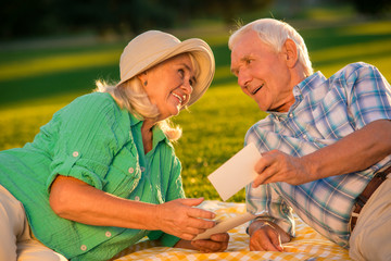 Senior couple is smiling. Man holding a photograph. Our first photo together. Most precious memories.