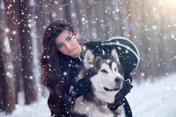 Attractive woman with the dogs. Fairy tale girl with Huskies or Malamute. Christmas.