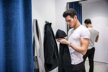 Young Handsome Man Trying on Clothes in Clothing Store's Changing Room in Front of a Mirror or in Room Closet