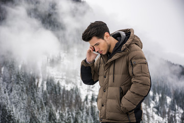 Dark haired handsome young man in winter outerwear using cell phone or smartphone, outdoor at mountain with snowy landscape behind