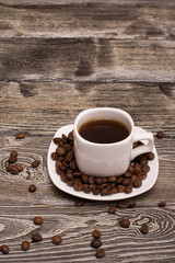 small white cup of coffee with cocoa beans on wooden background