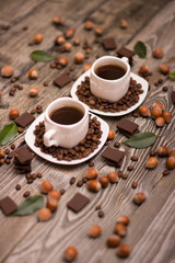 two small white cups of coffee with cocoa beans, slices of chocolate, hazelnuts and green leaves on wooden background