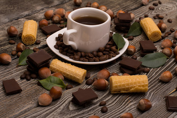 two small white cups of coffee with, cookies, cocoa beans, slices of chocolate, hazelnuts and green leaves on wooden background
