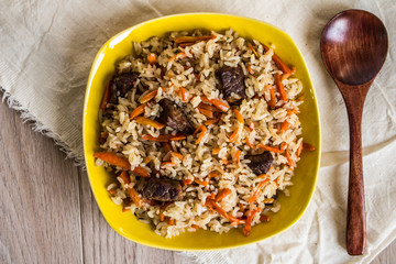Photo of dish of uzbek pilaf made of rice and carrots, meat and onions