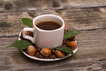 small white cup of coffee with cocoa beans, hazelnuts and green leaves on wooden background
