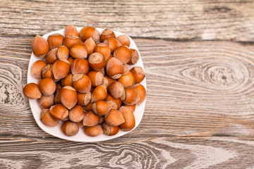 small white saucer with hazelnuts on wooden background
