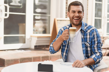 Handsome man relaxing with cup of latte