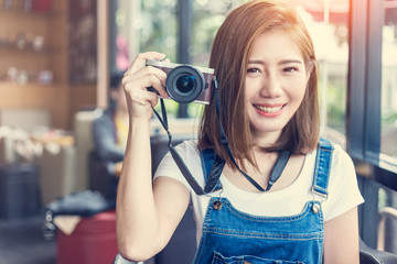 beautiful asia girl with camera in cafe