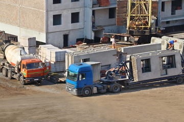 Concrete mixer, truck, workers on construction site with new bui