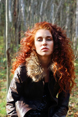 Beautiful woman in leather jacket poses in sunny autumn forest