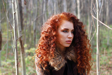 Beautiful woman with curly hair in leather jacket poses in sunny