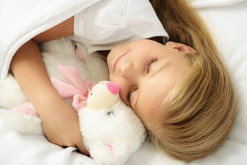 child sleeping on a couch with toy