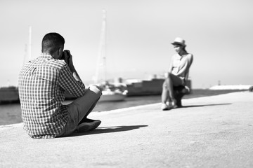 Young photographer taking picture of his girlfriend in seaport harbor
