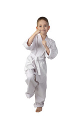 Karate boy stands in stance full height isolated on white background