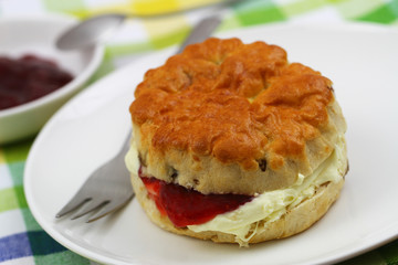 Freshly baked English scone with traditional clotted cream and strawberry jam on white plate