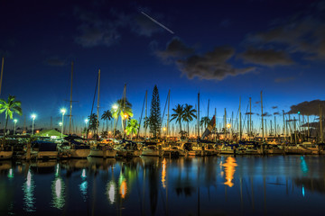 Sailing boats and yachts docked at the Ala Wai Harbor, the largest yacht harbor of Hawaii, reflecting in the sea. Honolulu harbor by night, Oahu, Hawaii.