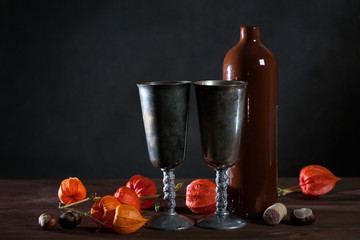 Autumn still life with wine bottle, metal cups, physalis and chestnuts