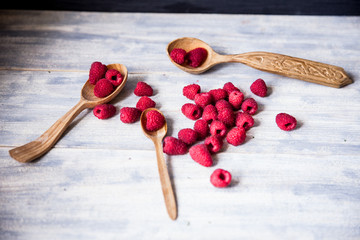 Ripe sweet raspberries in spoons on wooden table. Close up, top