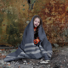 Little girl sits in basement wrapped in blanket and crying with tears on face - orphan, homelessness, poverty, despair concept