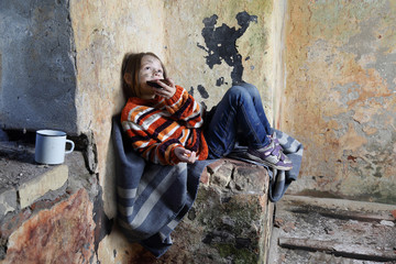 Sad little girl with dirty face sits on old blanket in basement and eats rough black bread - refugee orphan, hunger concept