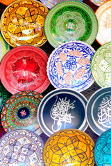 Traditional colorful Moroccan faience pottery dishes in a typical ancient shop in the Medina's souk of hte ancient imperial city of Marrakech, Morocco.