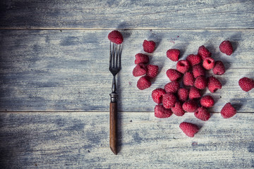 Ripe sweet raspberries in fork on wooden table. Close up, top vi