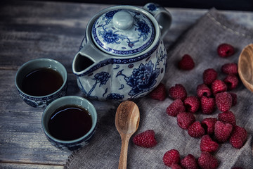 Ripe sweet raspberries in spoons on wooden table with tea pot. C