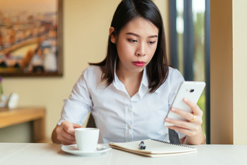 Young woman using smartphone with a coffee cup and notebook.