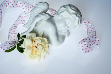Engelchen liegend mit Herzchen- Geschenkband und weißer Rose