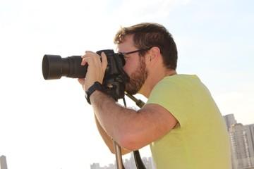 Homem fotografando paisagens urbana.
