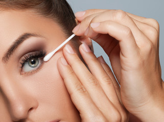 Woman with a cotton swab beside her eye