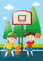 Two boys playing basketball in court