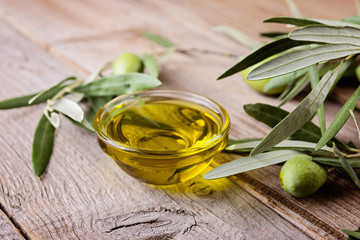 Olive oil and  branches on a wooden rustic background