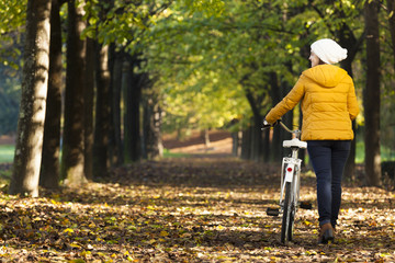 Beautiful smiling young woman walking with bicycle in Autumn par