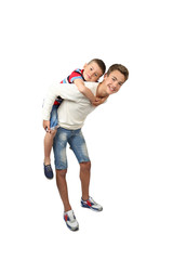 Older boy carries little brother on back isolated on white background