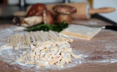 tagliatelle fresche, funghi porcini e prezzemolo su un tavolo infarinato