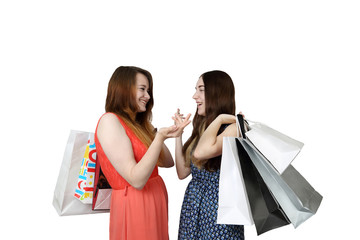 Two pretty girls with shopping bags chatting isolated on white background