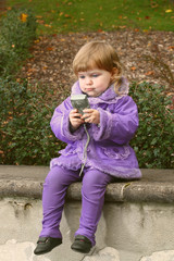 Little girl tries to use camera for self picture with a concentrated expression on her face in autumn park outdoor