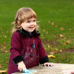 Little girl draws colored chalk on natural background outdoor