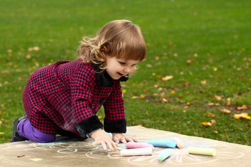 Little girl draws colored chalks standing on her knees on natural background outdoor