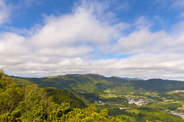 Aerial view of Sao Miguel Island with mountains and small villages, Azores, Portugal. Island landscape in summer when clouds are lifting on the horizon.