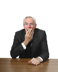 Shocked man sits at table covering her mouth by hand isolated on white background