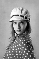 Young serious woman in cap and polka dots shirt black and white portrait