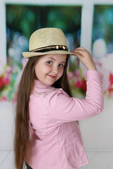Cute long haired plump girl in hat portrait - children beauty and fashion concept