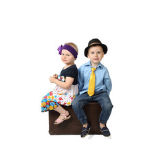Little boy and girl in retro festive clothes sit on vintage suitcase isolated on square white background