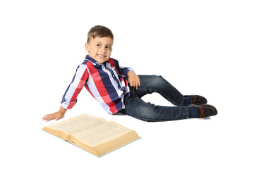 Cute Arabic looking little boy lies on floor with big book isolated on white background
