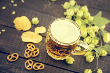 Beer and snacks on black wooden table. Draft cold beer in glass