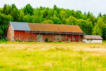 Old barn or farmhouse with makeshift wooden scaffolds outside.